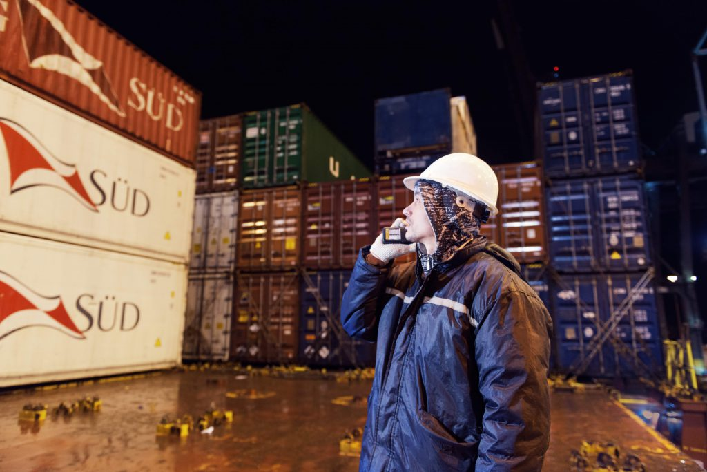 Ship worker making a phonecall amongst containers